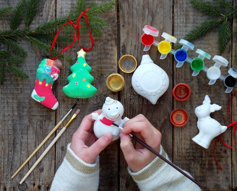Malerei spielt für Weihnachtsdekorationen vom Porzellan mit Ihren eigenen Händen Kind-` s DIY Konzept Herstellung der Weihnachtsb stockfoto