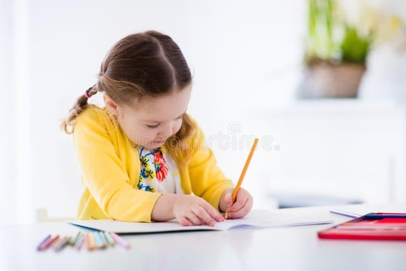 Malerei und Schreiben des kleinen Mädchens stockfotografie