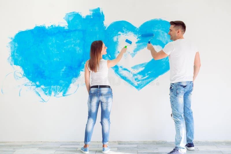 Malereiw?nde des gl?cklichen Paars in ihrem neuen Haus bereit zu zusammenleben stockfotografie