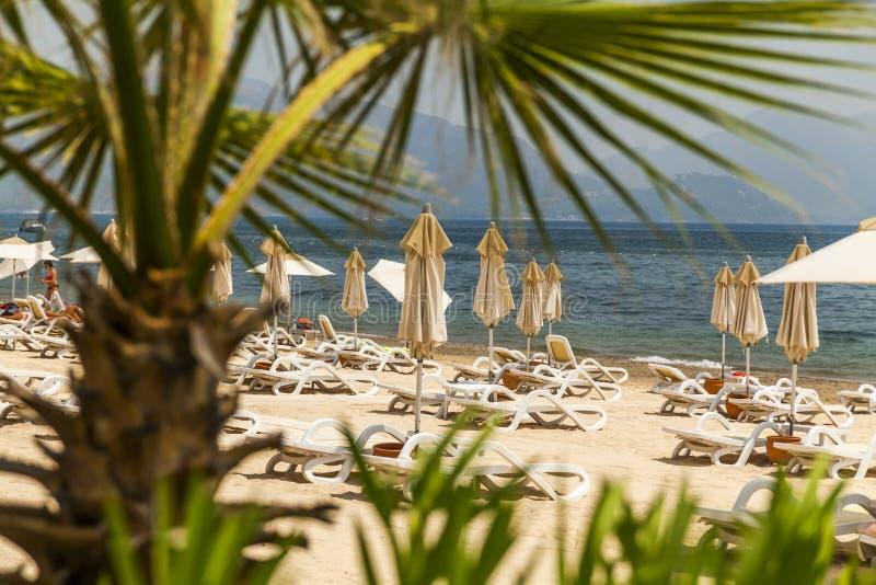 Malerische Ansichten des sandigen Strandes mit sunbeds stockbilder