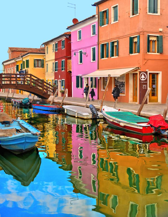Malerische Straße Burano-Insel mit kleinen farbigen Häusern, Touristen auf Holzbrücke und schönen Wasserreflexionen lizenzfreie stockfotografie
