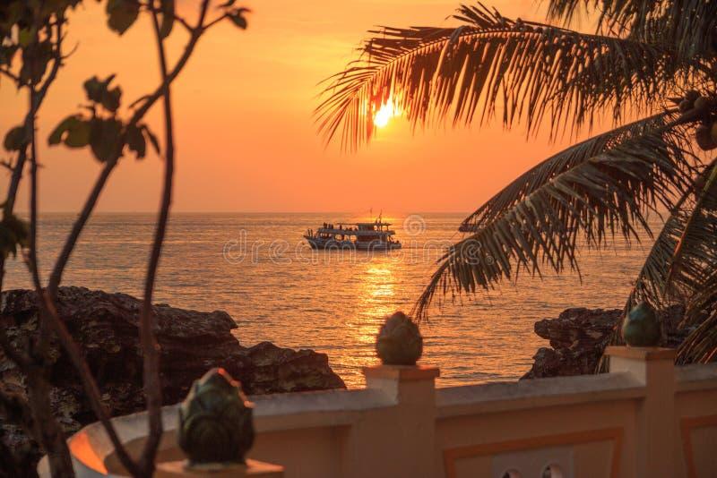 Malerischer Sonnenuntergang nahe dem Meer mit KokosnussPalme, orange Sonne, Boot und Wolken Phu Quoc, Vietnam lizenzfreie stockfotos