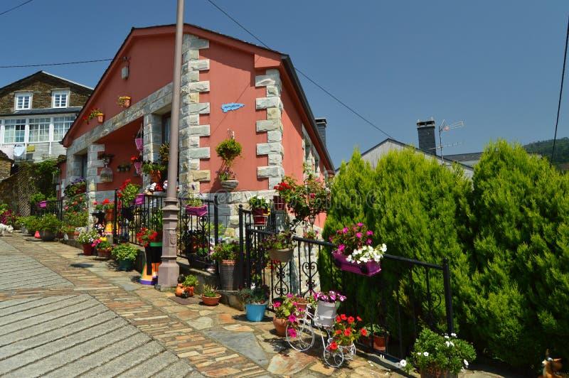 Malerisches Haus umgeben durch die Blumen-Töpfe, die verziert werden und Anlagen um es in Taramundi, Asturien, Spanien ermangelt  stockfotografie