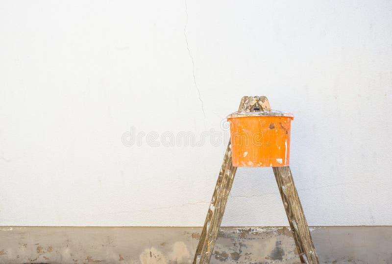 Malerleiter und Eimer vor einer leeren Außenwand lizenzfreies stockfoto