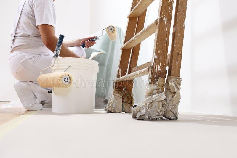 Malermann bei der Arbeit mit einer Rolle, einem Eimer und einer Leiter stockfotografie