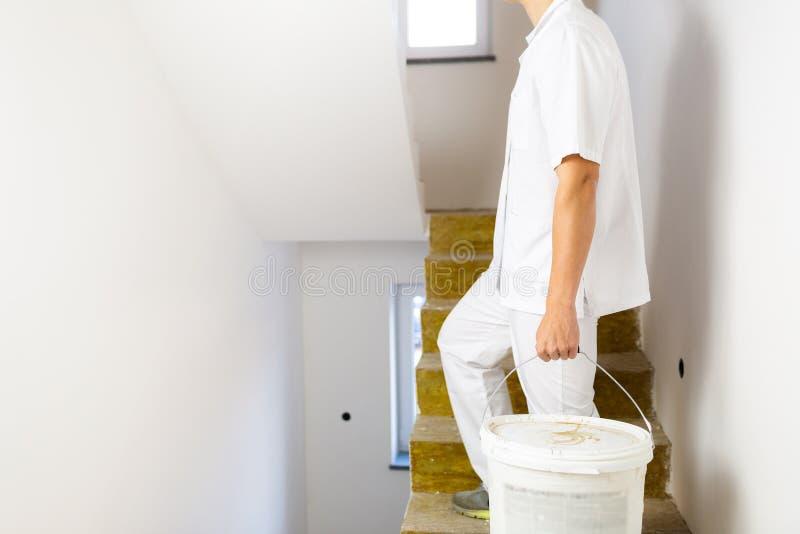 Malermann, der in den weißen Wänden einer Hausmalerei arbeitet stockbild