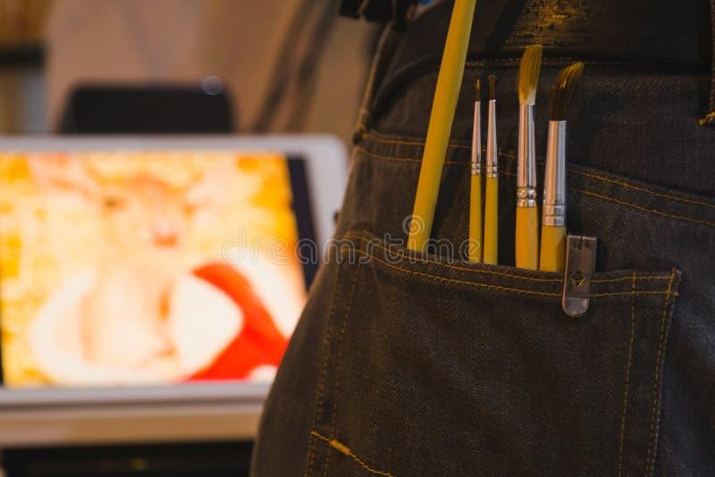 Malerpinsel in der Tasche von Jeans mit unscharfem Bildhintergrund stockfotos
