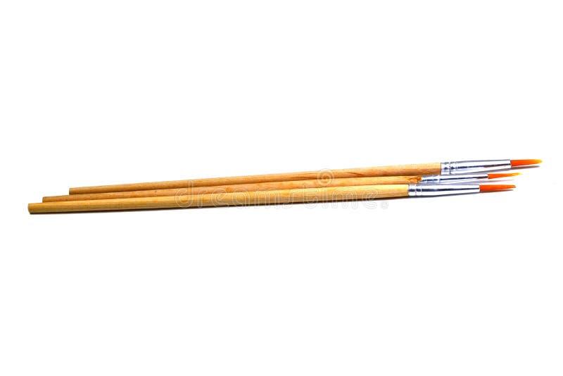 Malerpinsel drei mit Holzgriff auf dem weißen Hintergrund lokalisiert stockbilder