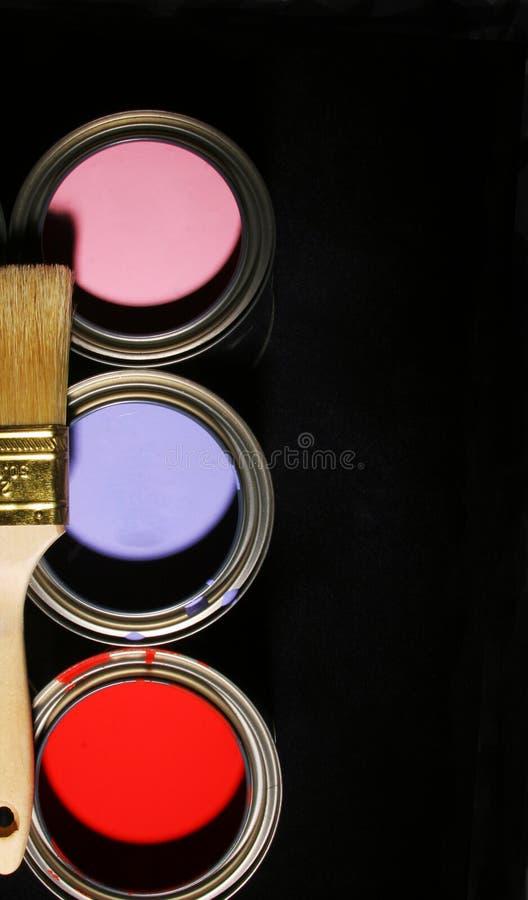 Malerpinsel und Dosen farbige Hauptlacke auf schwarzem Backgroun lizenzfreie stockfotos