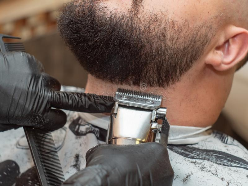 Males beard cutting with clipper and black comb, close up view. Stylistd hands in black rubber gloves. Master at work in. Hairdressing saloon. Selective soft stock images