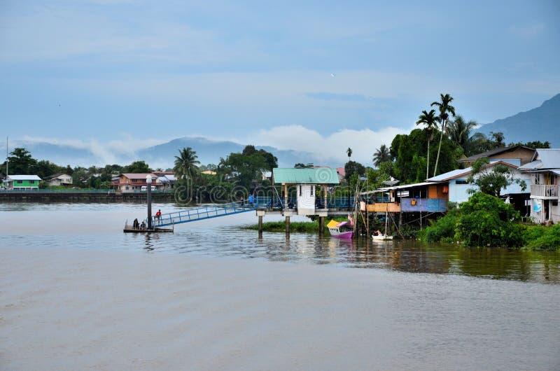 Malesi dal villaggio della riva del fiume di Sarawak sul molo con le montagne Kuching Malesia fotografia stock libera da diritti