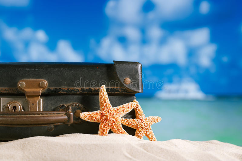 Maleta antigua retra vieja en la playa con las estrellas de mar, el océano y el cielo foto de archivo