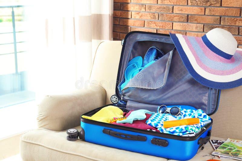 Maleta con diversos ropa y accesorios en el sofá dentro El embalar para las vacaciones imágenes de archivo libres de regalías