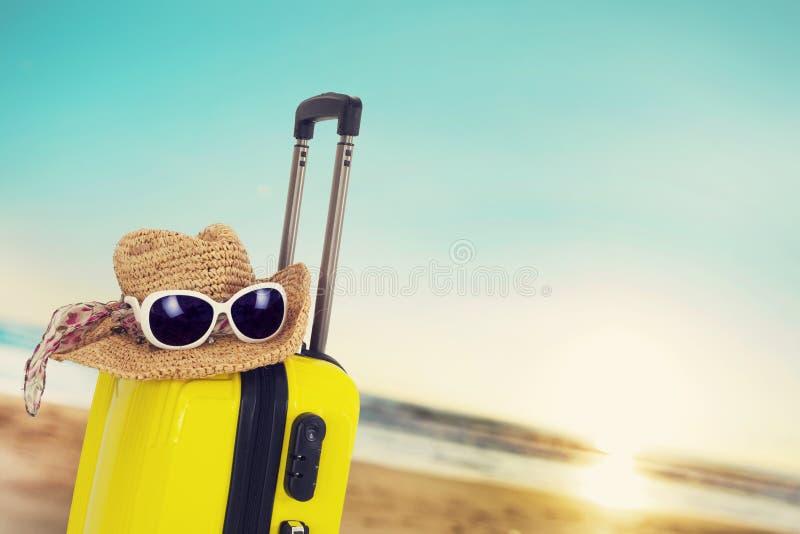 Maleta con el sombrero en la playa imagen de archivo