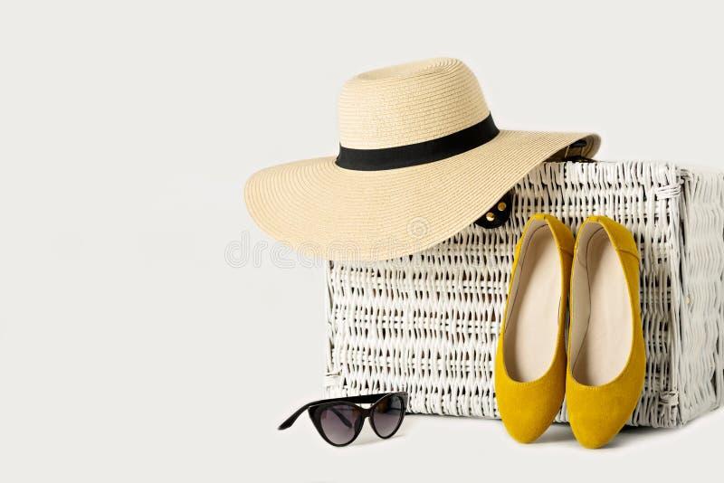 Maleta de mimbre blanca, sombrero para mujer, gafas de sol y zapatos amarillos imagen de archivo libre de regalías