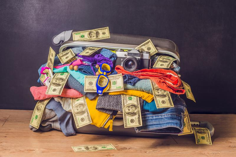Maleta llena con los accesorios y el dinero del viaje en la parte posterior de madera fotos de archivo libres de regalías