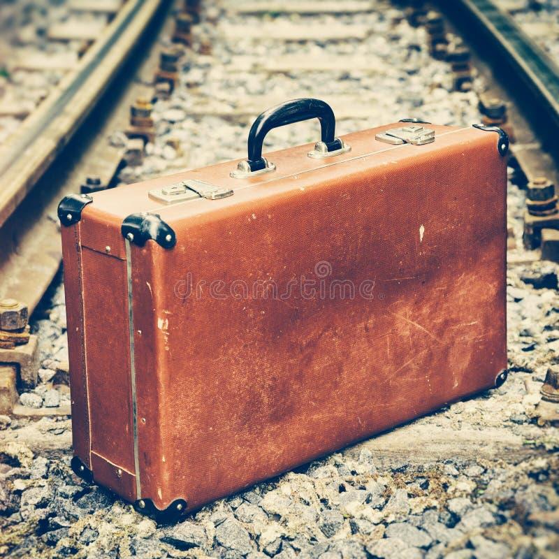 Maleta vieja en el ferrocarril foto de archivo