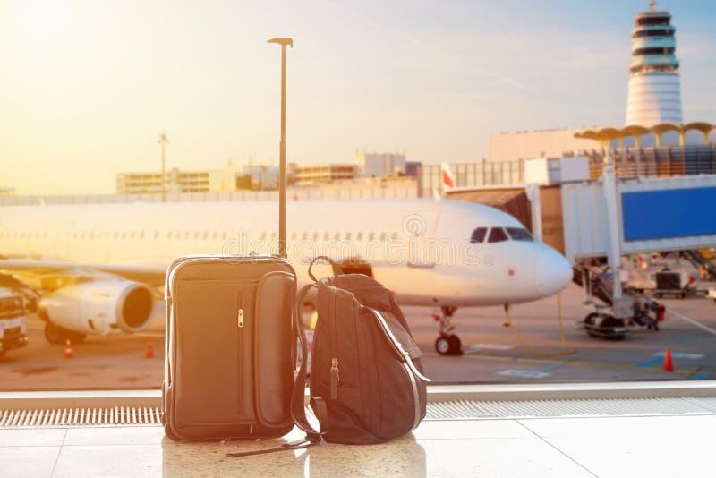 Maleta y bolso del hombre de negocios contra el avión de aire en el fondo en terminal de aeropuerto durante puesta del sol Concep fotografía de archivo