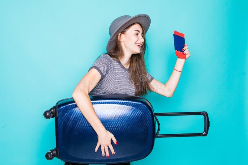 Maleta y pasaporte de la tenencia de la mujer joven que parecen para arriba aislados en fondo azul imagen de archivo