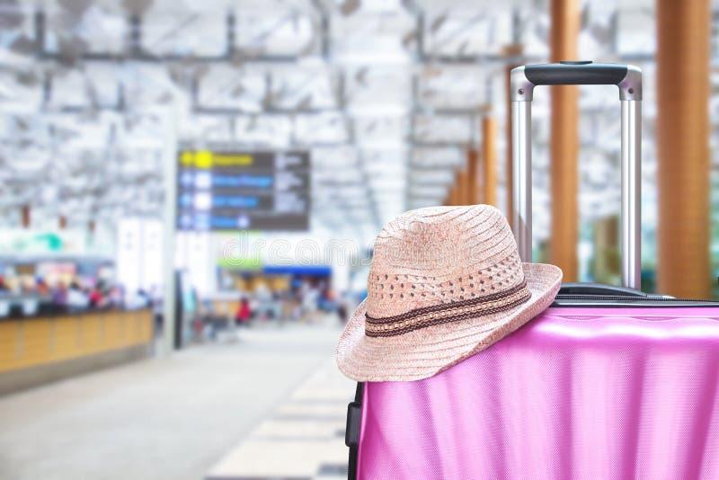 Maleta y sombrero en el aeropuerto imágenes de archivo libres de regalías