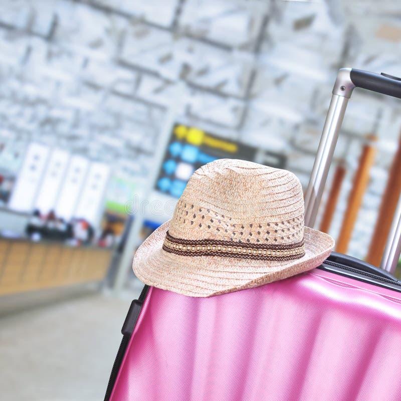 Maleta y sombrero en el aeropuerto imagen de archivo
