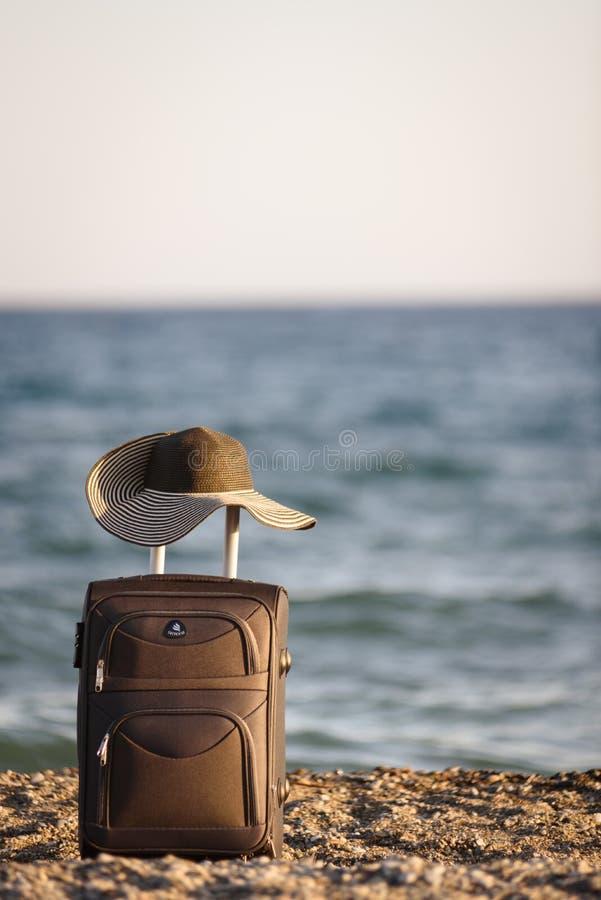 Maleta y sombrero en la playa fotografía de archivo