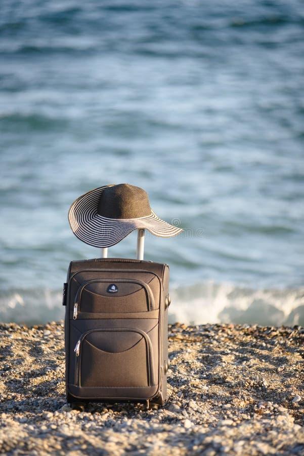 Maleta y sombrero en la playa imagen de archivo libre de regalías