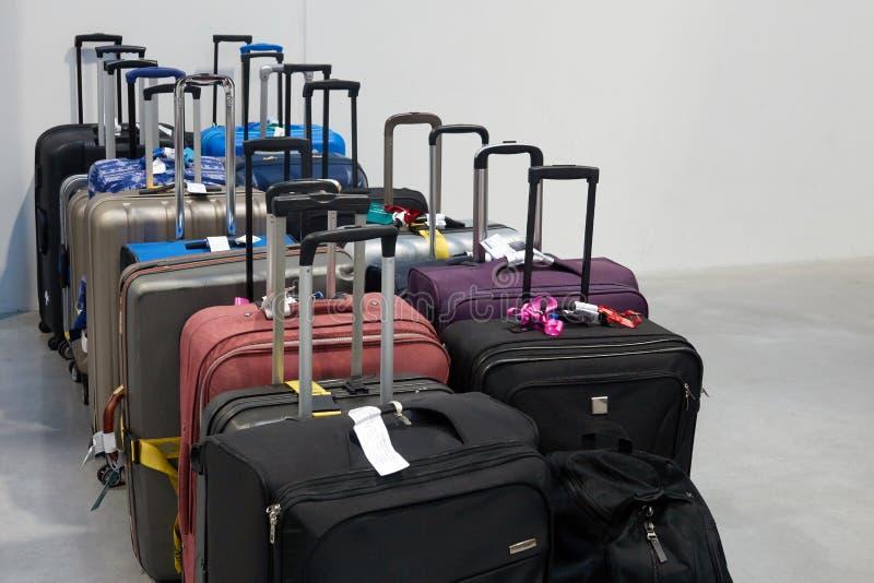 Maletas de los viajeros con las etiquetas coloreadas en la zona de espera imagen de archivo libre de regalías