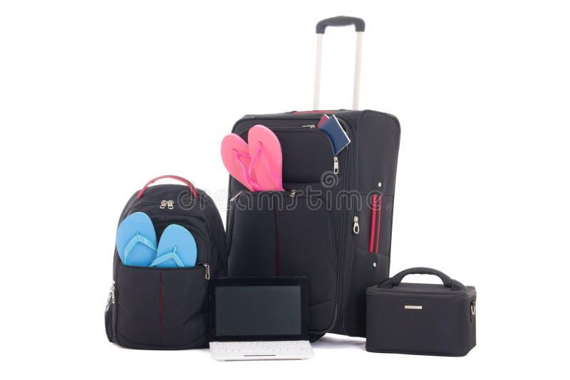 Maletas del viaje, mochila con la ropa, ordenador portátil aislado en whi fotografía de archivo