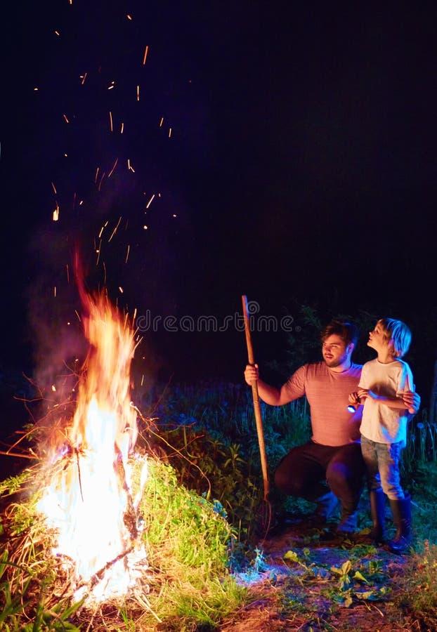 Maleza ardiente de la familia en el fuego, limpieza estacional del área del campo, forma de vida del pueblo foto de archivo