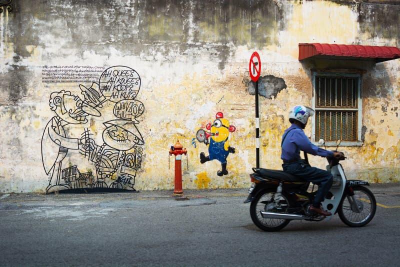 MALEZJA, PENANG, GEORGETOWN - OKOŁO JUL 2014: Mężczyzna na motorcyc obraz stock