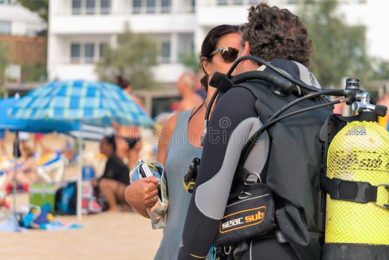 Malgrat de Fördärva, Catalonia, Spanien, Augusti 2018 Flickan eskorterar dykaren, innan han dyker in i havet på stranden arkivfoton