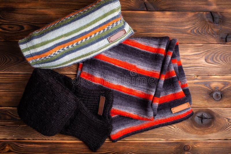 A malha listrada listrou scarves e as luvas feitas malha pretas no fundo de madeira imagens de stock royalty free