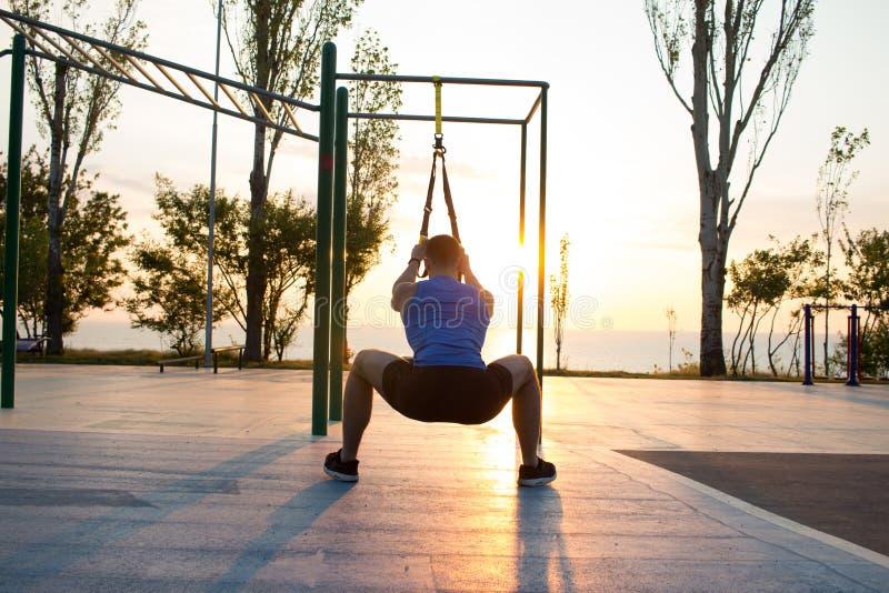 malhar com as correias da suspensão no gym exterior, no homem forte que treinam cedo na manhã no parque, no nascer do sol ou no p fotografia de stock