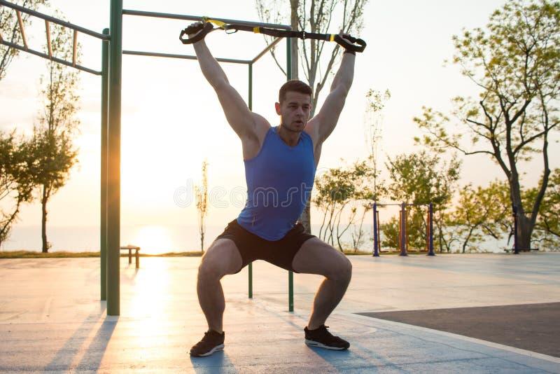 malhar com as correias da suspensão no gym exterior, no homem forte que treinam cedo na manhã no parque, no nascer do sol ou no p imagens de stock royalty free