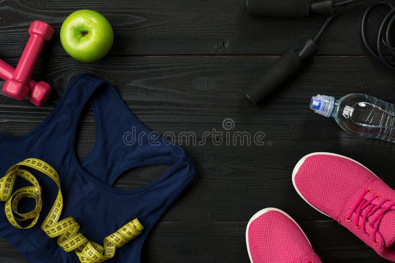 Malhar o plano com alimento e equipamento da aptidão no fundo escuro, vista superior foto de stock