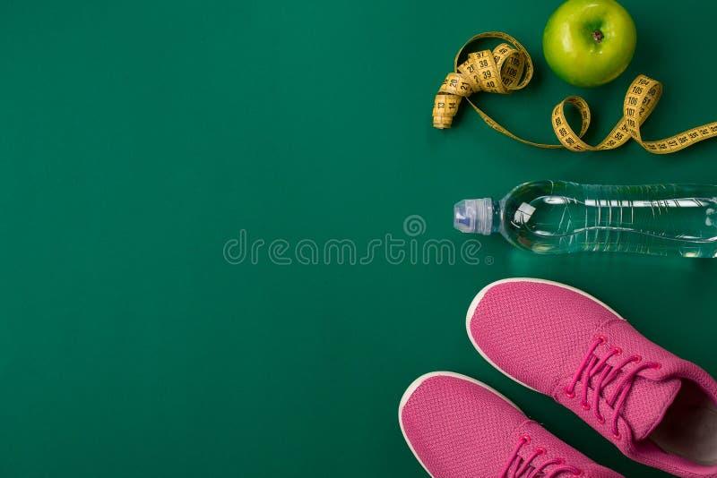 Malhar o plano com alimento e equipamento da aptidão no fundo verde, vista superior imagens de stock