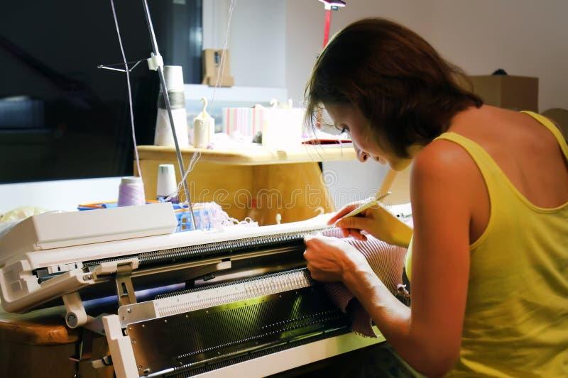 Malhas da mulher na máquina de confecção de malhas na noite Trabalho lateral do trabalho a domicílio em casa imagens de stock royalty free