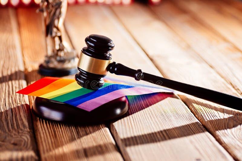 Malho de madeira do juiz - símbolo da lei e da justiça com a bandeira das cores do arco-íris do lgbt foto de stock