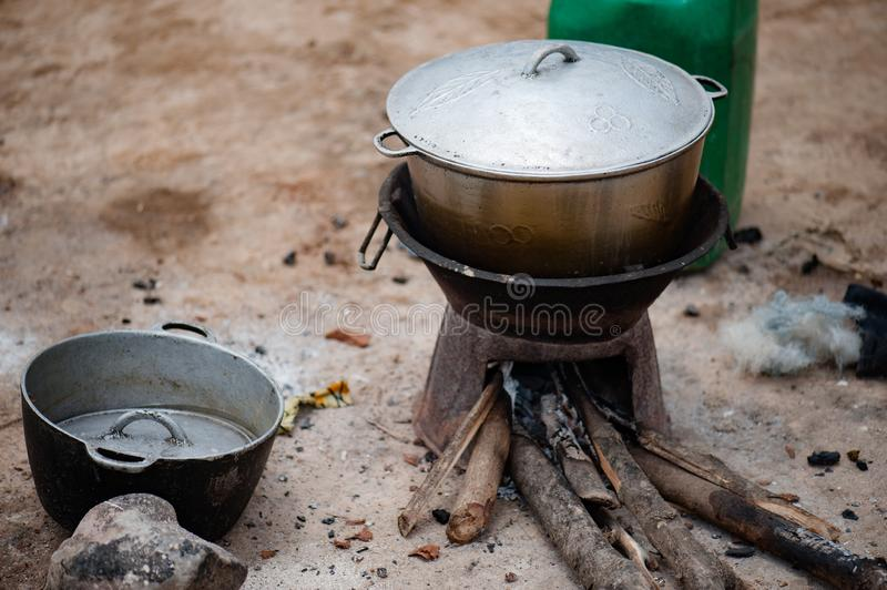 African pots on the dirty ground. Mali, Africa. Metallic pots places on the dirty ground in a village near Bamako royalty free stock image
