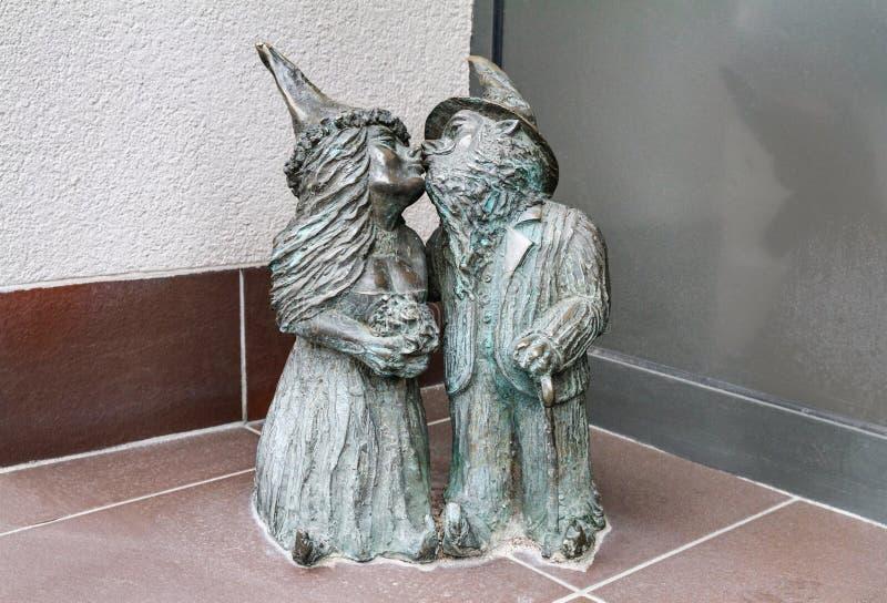 Mali brązowi statua gnomy imieniem - Nowozency, para gnomów nowożeńcy całować obrazy royalty free