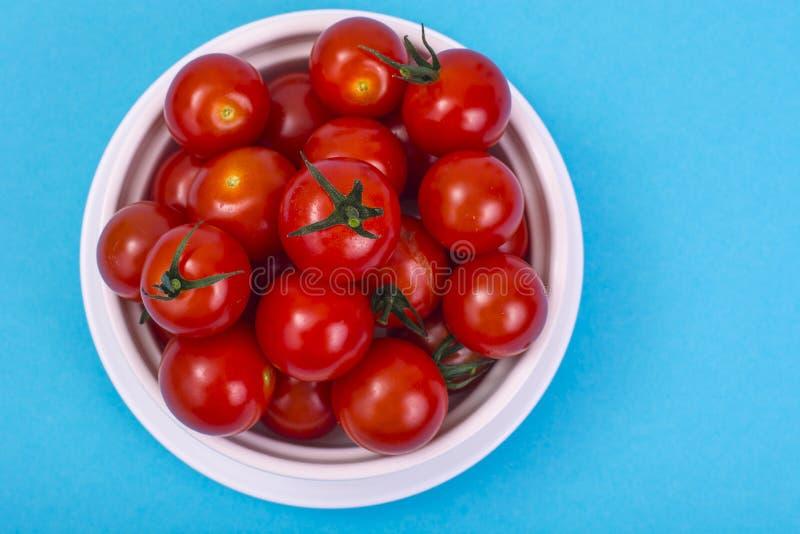 Mali czerwoni czereśniowi pomidory w bielu talerzu na błękitnym tle zdjęcia stock