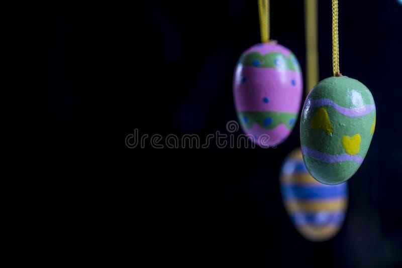 Mali drewniani malujący Wielkanocni jajka przeciw czarnemu tłu, Przestrzeń dla teksta zdjęcia stock