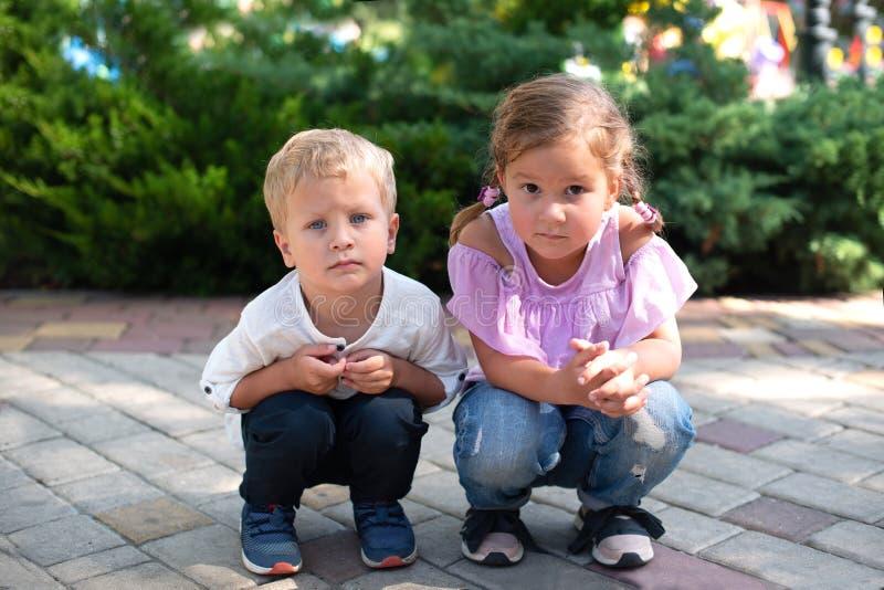Mali dzieci, dziewczyna, chłopiec, brat, siostra, kucnięcie i spojrzenie przy kamerą, ostrożnie, czekać na ptaka latać z fotografia royalty free