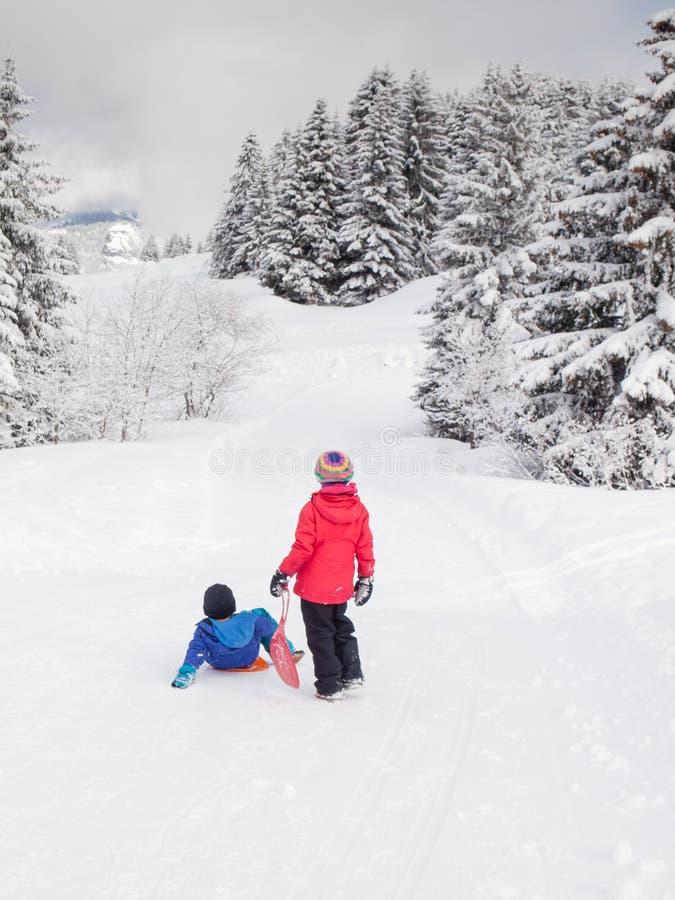 Mali dzieci w śniegu z saneczkami obraz royalty free