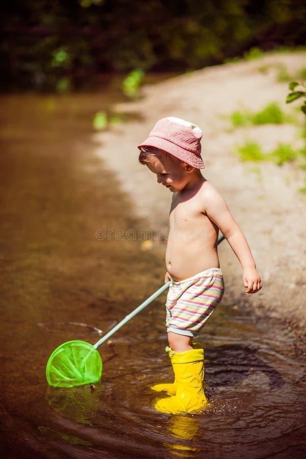 Mali dziecko chwyty ryba i żaby w rzece zdjęcia stock