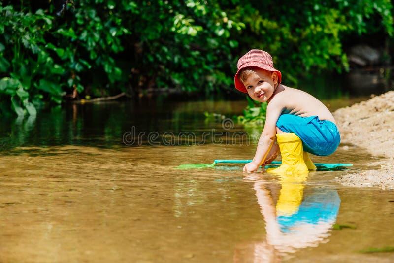 Mali dziecko chwyty ryba i żaby w rzece fotografia stock