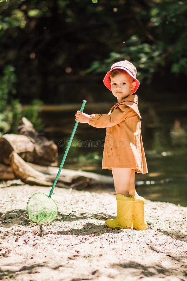 Mali dziecko chwyty ryba i żaby w rzece zdjęcie stock