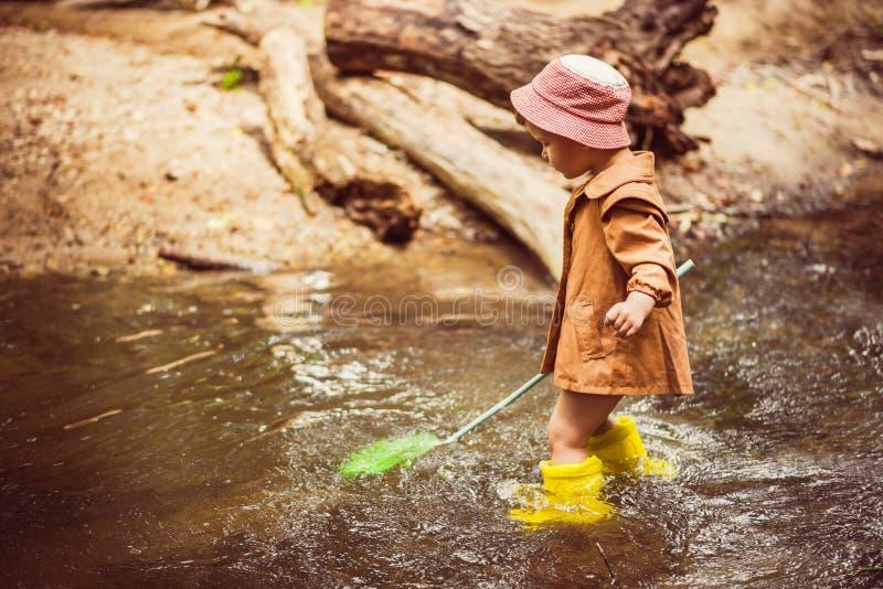 Mali dziecko chwyty ryba i żaby w rzece fotografia royalty free
