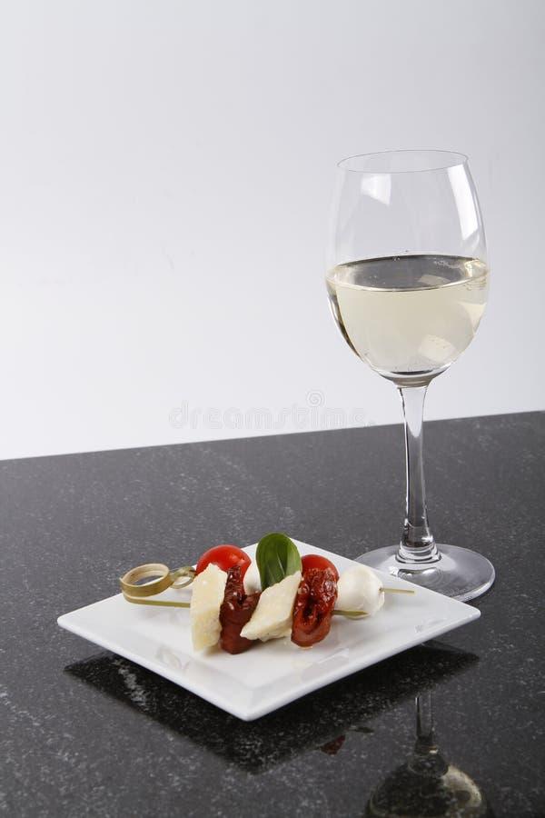 Mali kije na talerzu z białym winem fotografia stock